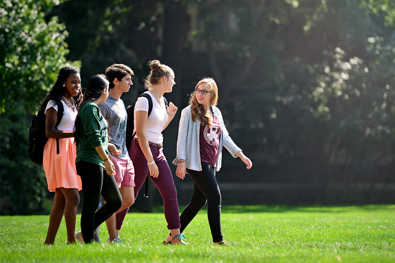 group of students walking on campus in-line