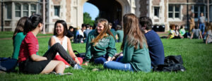 group of students sitting and talking on campus featured