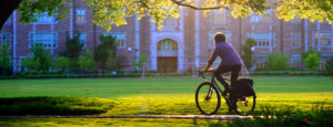 student riding bike on campus featured